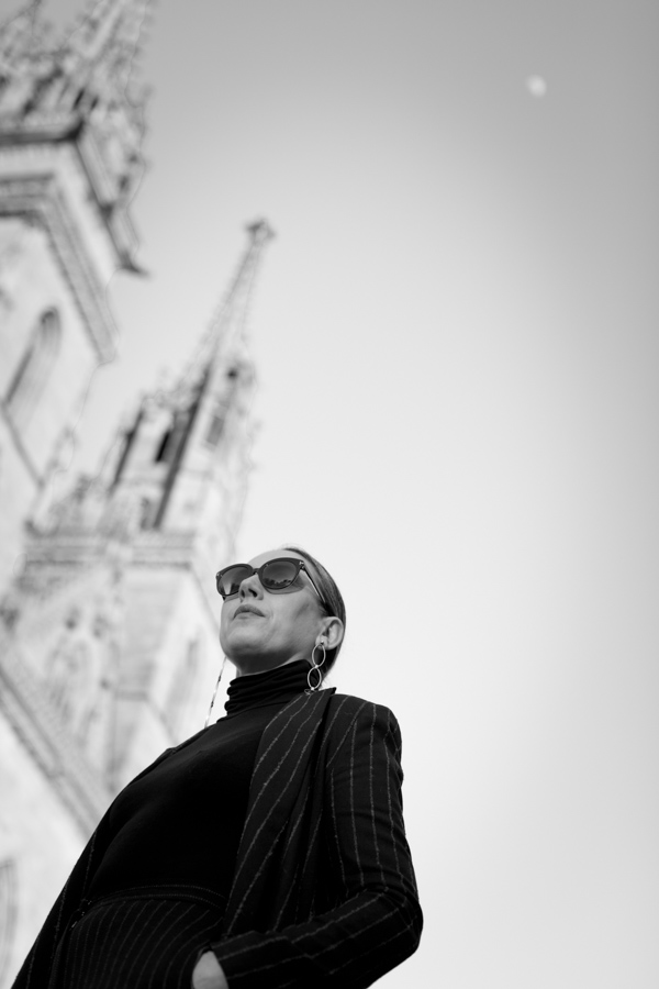 Woman in black in front of blurred cathedral in Basel