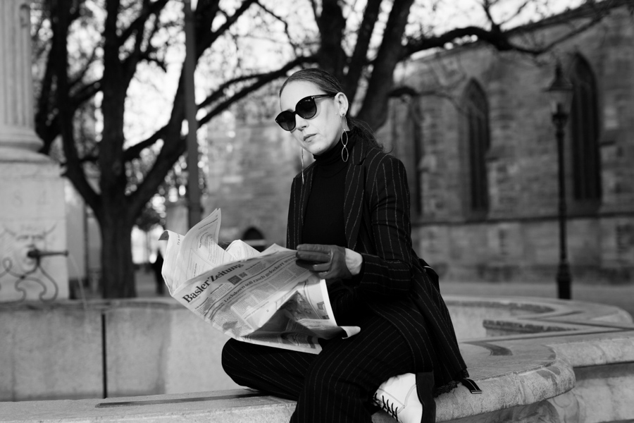 Woman in black with sunglasses sitting on fountain reading newspaper