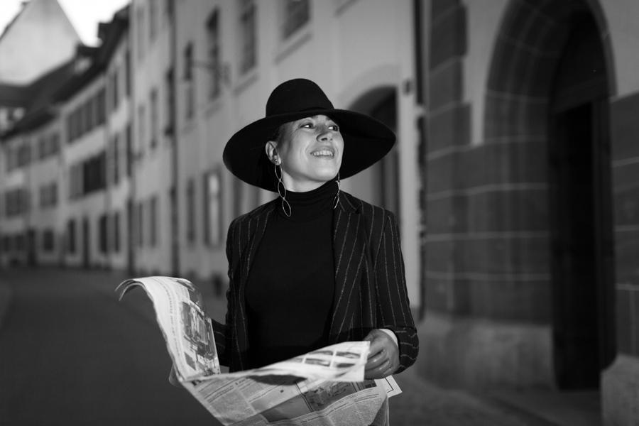 Woman in black hat on street holding newspaper