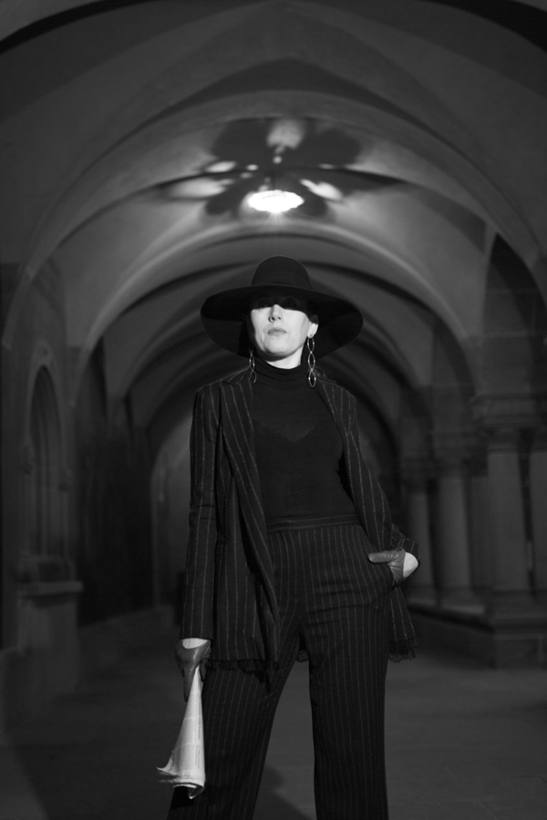 Woman in black suit and black hat under columns