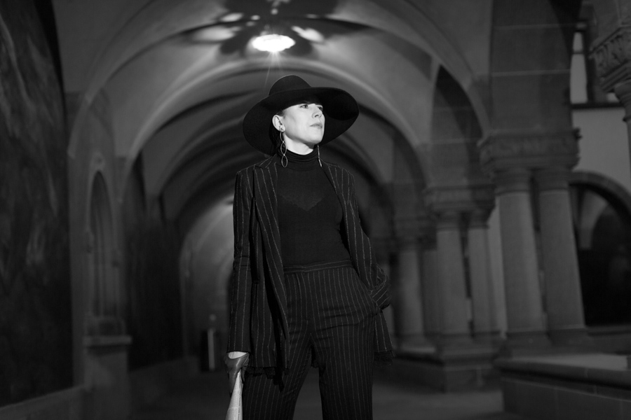 Women in black hat under colums black and white